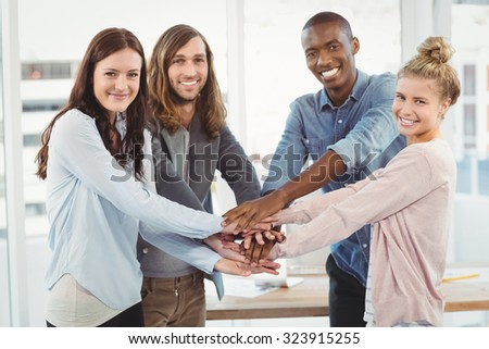 Portrait of smiling business team putting their hands together at office - stock photo