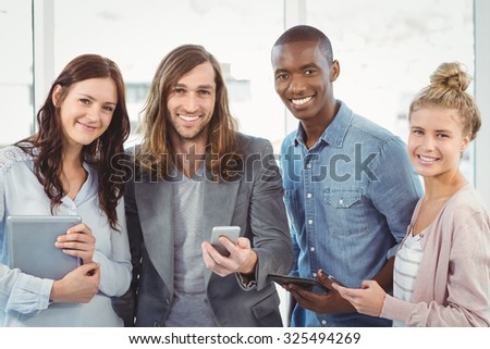 Portrait of smiling business team using technology while standing at office - stock photo