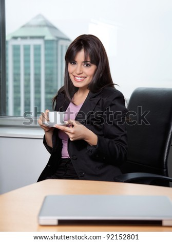 Portrait of smiling business woman having cup of coffee at office - stock photo