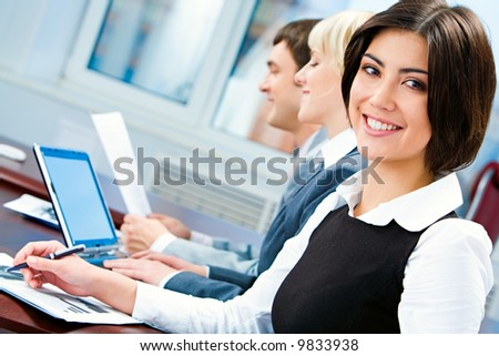 Portrait of smiling business woman looking at camera during working briefing - stock photo