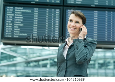 Portrait of smiling business woman on mobile phone in front of panel at airport - stock photo