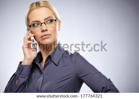 Portrait of smiling business woman phone talking, isolated on grey background  - stock photo