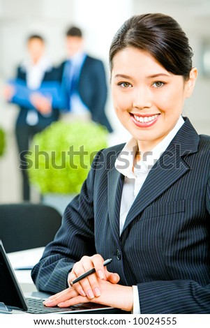 Portrait of smiling business woman sitting at the table