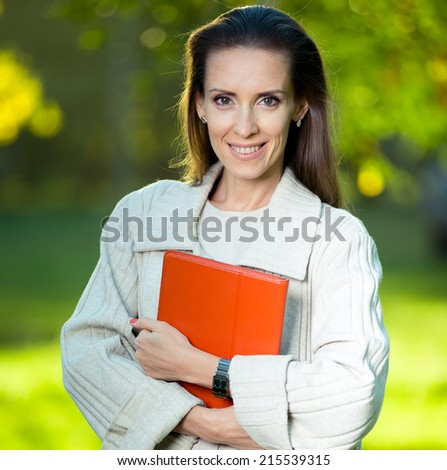 Portrait of smiling business woman with paper folder and pad, against green city park background. Student.