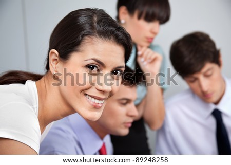 Portrait of smiling business woman with team working in background - stock photo