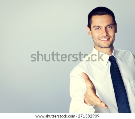 Portrait of smiling businessman giving hand for handshake, with blank copyspace area for text or slogan, specially toned - stock photo