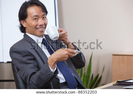 Portrait of smiling businessman having coffee - stock photo