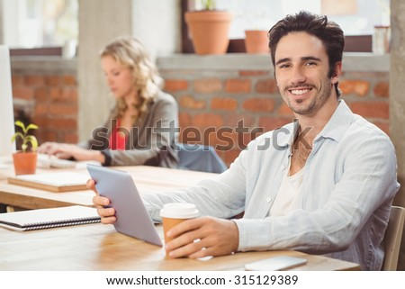 Portrait of smiling businessman holding digital tablet and coffee while sitting in creative office - stock photo