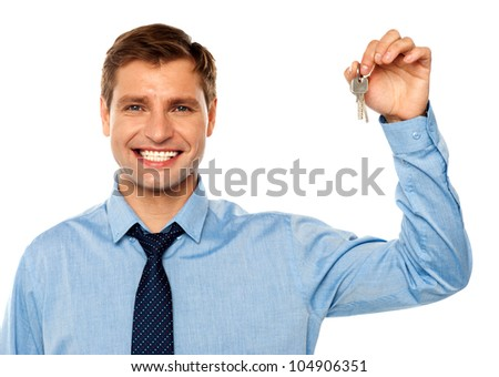 Portrait of smiling businessman holding keys isolated on white background