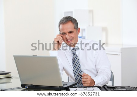 Portrait of smiling businessman in front of computer - stock photo