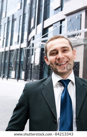 Portrait of smiling businessman in front of office building - stock photo