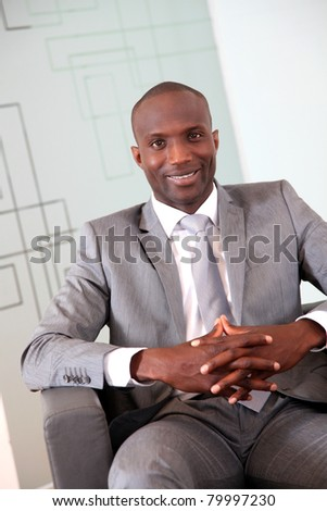 Portrait of smiling businessman in grey suit - stock photo