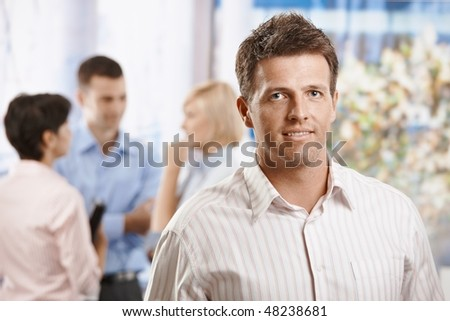 Portrait of smiling businessman in office, Colleagues talking in the background. - stock photo