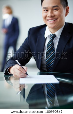 Portrait of smiling businessman looking at camera at workplace - stock photo