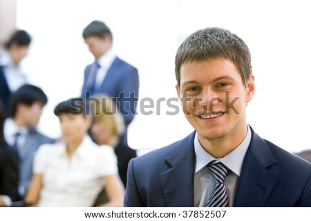 Portrait of smiling businessman looking at camera in working environment - stock photo
