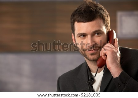Portrait of smiling businessman on landline phone call in office. - stock photo