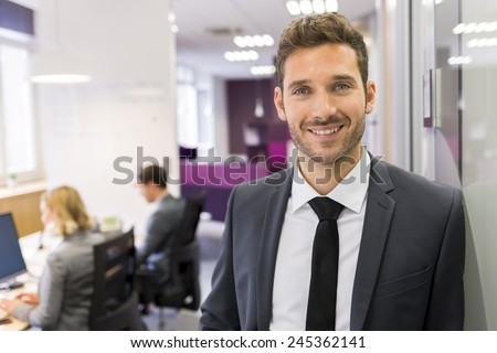 Portrait of smiling Businessman posing  in modern office, looking camera - stock photo