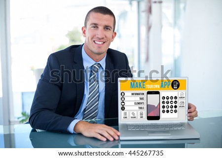 Portrait of smiling businessman showing laptop against white background with vignette - stock photo