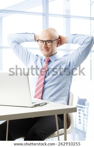 Portrait of smiling businessman sit back while sitting in front of laptop at office. Business people.  - stock photo