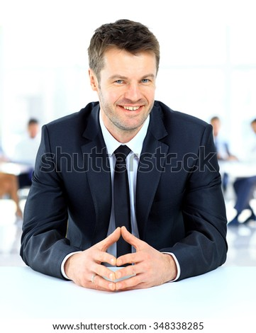 Portrait of smiling businessman sitting at a table of the background of his team - stock photo