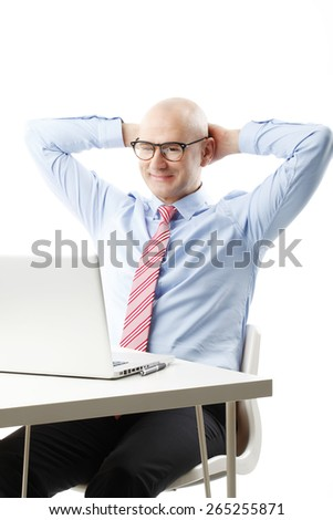 Portrait of smiling businessman sitting back while sitting at office in front of computer and reading business report. Isolated on white background.