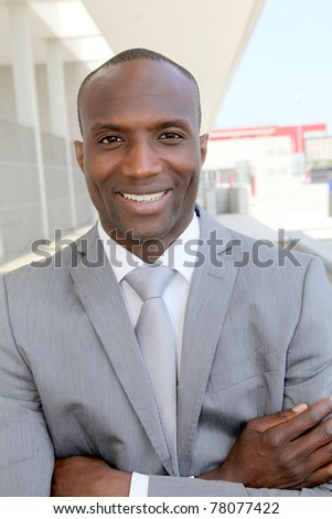 Portrait of smiling businessman standing outdoors - stock photo
