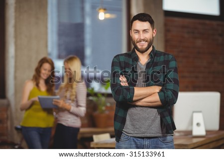 Portrait of smiling businessman standing with colleagues in background - stock photo