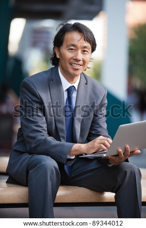 Portrait of smiling businessman using laptop outdoors - stock photo