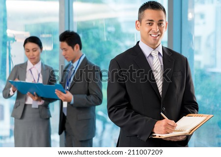 Portrait of smiling businessman with a notepad in hands