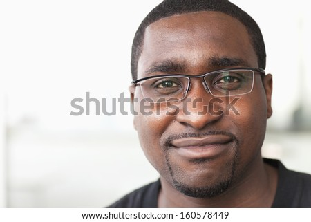 Portrait of smiling businessman with glasses looking at camera