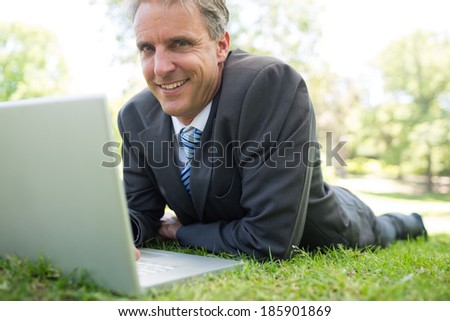 Portrait of smiling businessman with laptop lying on grass in park