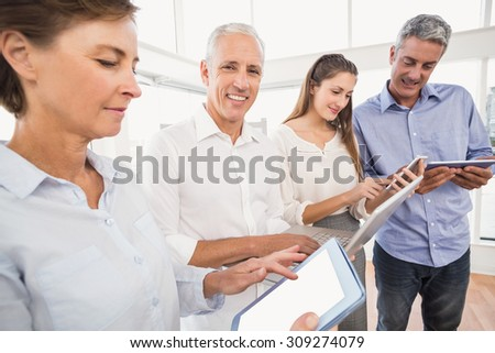 Portrait of smiling businessman with laptop next to colleagues in the office
