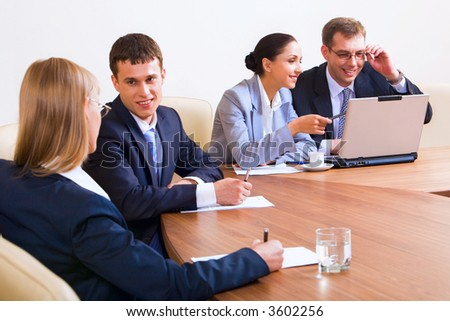 Portrait of smiling businesspeople discussing different questions sitting around the table with an opened laptop, documents and glasses of water - stock photo