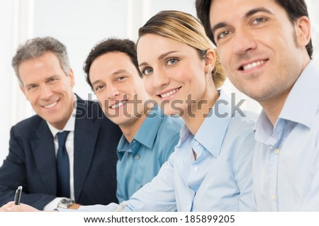 Portrait Of Smiling Businesspeople Looking At Camera Sitting In A Row - stock photo