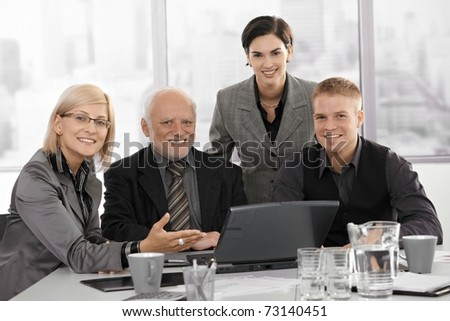 Portrait of smiling businessteam at work looking at camera, businesswoman gesturing at laptop computer.? - stock photo