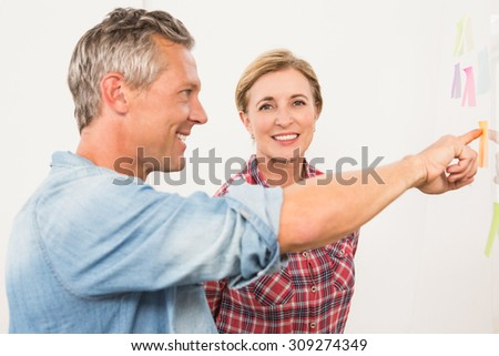Portrait of smiling businesswoman brainstorming with colleague in the office - stock photo
