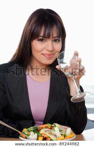 Portrait of smiling businesswoman drinking water with salad on table - stock photo