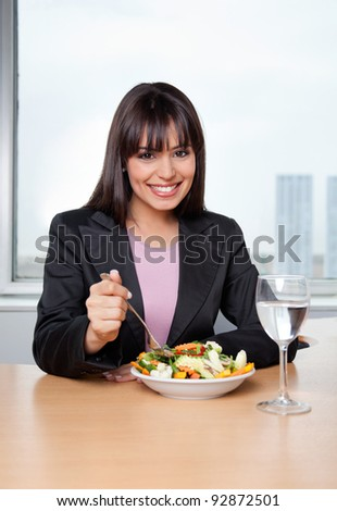 Portrait of smiling businesswoman having fresh vegetable salad with glass of water on desk - stock photo