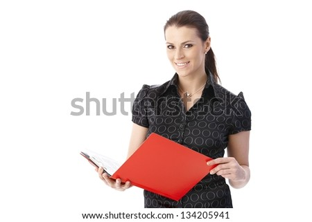 Portrait of smiling businesswoman holding documents in red folder, looking at camera, isolated on white.