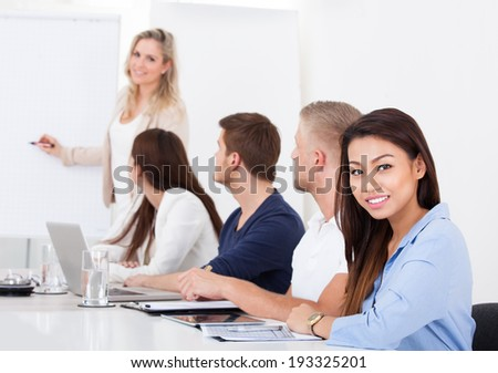 Portrait of smiling businesswoman sitting with colleagues in meeting at office - stock photo