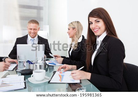 Portrait of smiling businesswoman sitting with colleagues in meeting at office