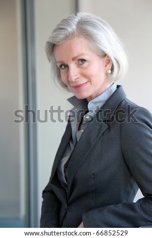 Portrait of smiling businesswoman standing in office - stock photo