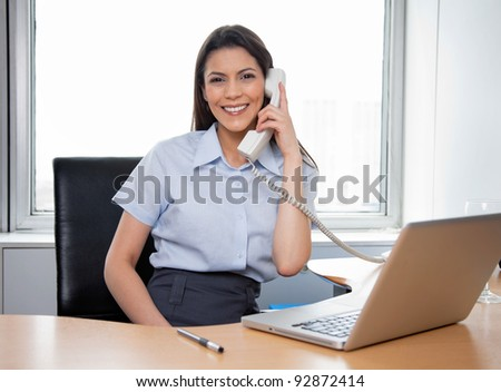 Portrait of smiling businesswoman talking on phone with laptop on her desk - stock photo