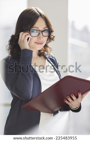 Portrait of smiling businesswoman using cell phone while holding file in office - stock photo