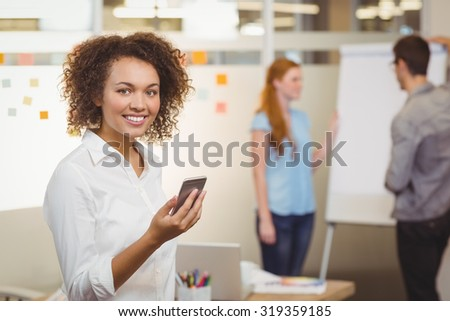 Portrait of smiling businesswoman using mobile phone in office with colleagues discuccing in background - stock photo