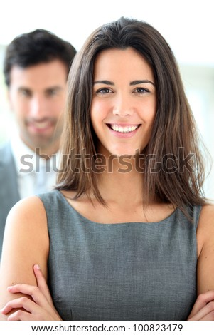 Portrait of smiling businesswoman wearing grey dress - stock photo
