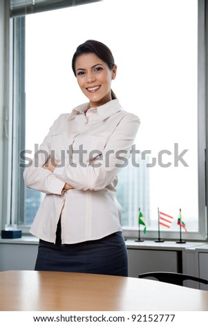 Portrait of smiling businesswoman with arms crossed standing in office - stock photo
