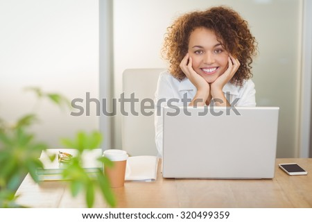 Portrait of smiling businesswoman with hand on chin sitting by laptop on desk in office - stock photo