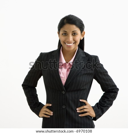 Portrait of smiling businesswoman with hands on hips against white background.