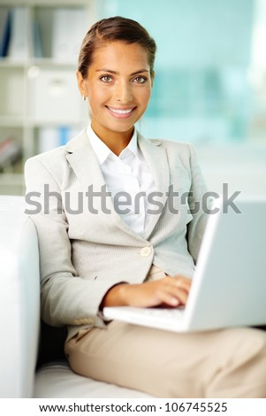 Portrait of smiling businesswoman with laptop in office - stock photo